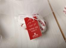 שקית טול עם נשיקה מודפסת וסוכריות סודה לבבות.  כולל שם הכלה והחתן עם תאריך האירוע על גבי טיקט חיצוני.
